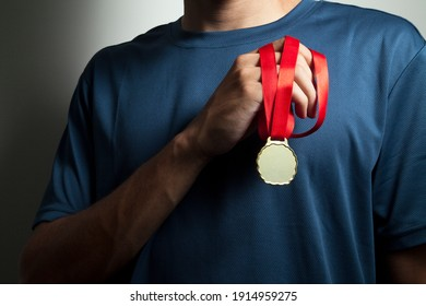 Athlete holding gold medal with his hands. Medal concept.