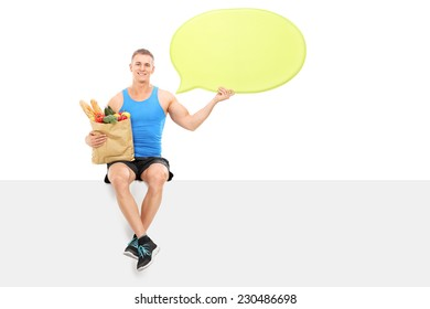 Athlete holding a speech bubble and grocery bag seated on a panel isolated on white background