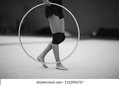 Athlete with a hoop for an exercise in rhythmic gymnastics in a training hall