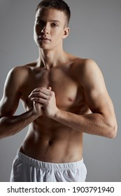 athlete with inflated torso joined hands near chest on gray background