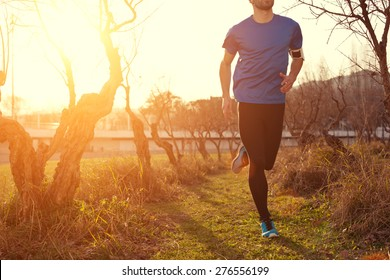 Athlete jogging in the park at sunset (little motion blur, intentional sun glare)
