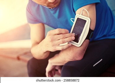 athlete listening music and touching armband for smartphone (intentional sun glare)