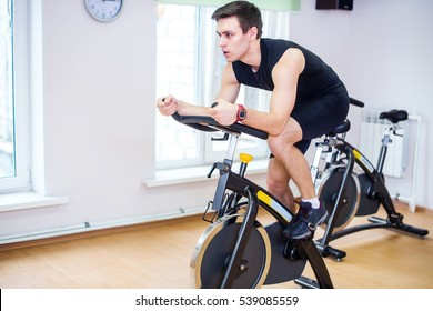 Athlete man biking in the gym, exercising his legs doing cardio training cycling bikes