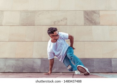athlete man dancer in a white T-shirt, jeans glasses, dancing, summer in the city, background wall, active hip hop, youth lifestyle, stunt break dance, street and artist
