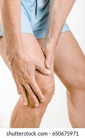 Athlete man feeling pain to the knee and the quadriceps. It could be Iliotibial band syndrome or quadriceps tendinopathy