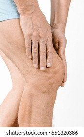 Athlete man massaging a painful  quadriceps and the knee after a sport accident. It could be a quadriceps tendinopathy, a muscle elongation, a medial meniscus tears or bursitis