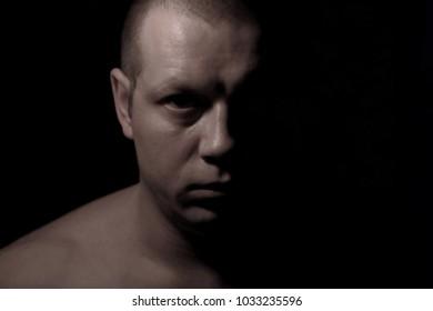 Athlete man portrait in darkness.