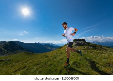 Athlete man practicing mountain running in the sun at high altitude.