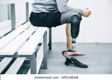 Athlete man with prosthetic leg sitting in gym locker room