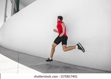 Athlete man running away sprinting doing cardio hiit workout exercise training at outdoor summer gym. Male runner jogging.