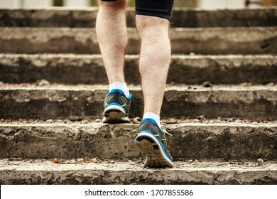 Athlete man running on concrete stairs, close-up of legs in sneakers.