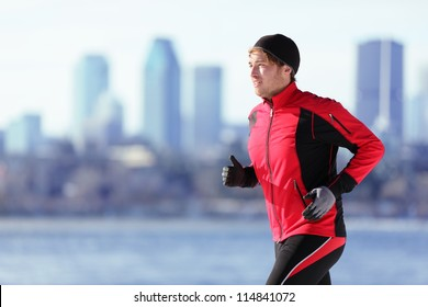 Athlete man running sport. Runner in winter jogging outdoors with city skyline in background. Male fitness model in Montreal, Canada.
