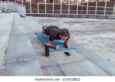 athlete man in summer in city, stands on bar, trains abdominal muscles and press, yoga mat, phone application in smartphone online timer, shaker with water protein