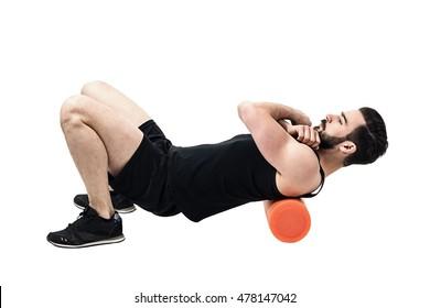 Athlete massaging upper back muscles with foam roller. Full body length portrait isolated on white studio background.