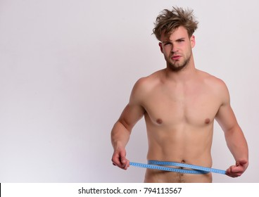 Athlete with messy hair measures waist or sixpacks. Guy with serious face isolated on light grey background, copy space. Man with blue measuring tape around naked torso. Sports and weight loss concept