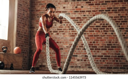 Athlete moving the ropes in wave motion as part of fat burning workout in fitness studio. Sportswoman exercising with battling ropes at gym.