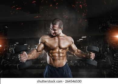 Athlete muscular bodybuilder in the gym training with dumbbells