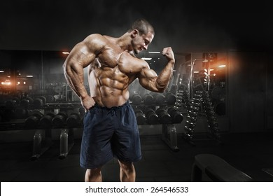 Athlete muscular bodybuilder man demonstrates his muscles in the gym