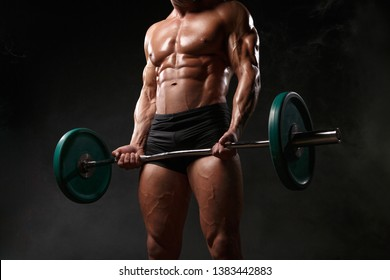 Athlete muscular bodybuilder on black background with barbell