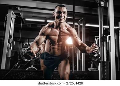 Athlete muscular bodybuilder training chest on simulator in the gym
