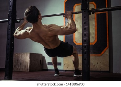 Athlete muscular fitness male model pulling up on horizontal bar in a sport-club.
