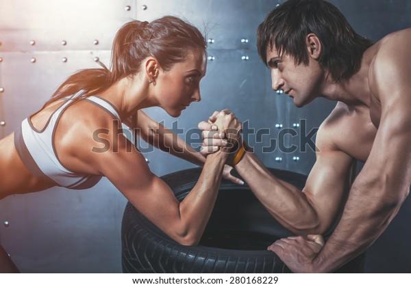 Atleta deportistas musculares hombre y mujer con las manos atadas desafío de lucha libre entre una pareja joven Crossfit fitness entrenamiento de estilo de vida bodybuilding concepto