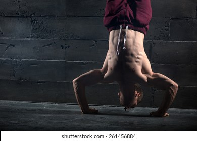 Athlete with naked torso doing push-ups on his hands while standing upside down near the concrete wall. Studio shots in the dark tone.