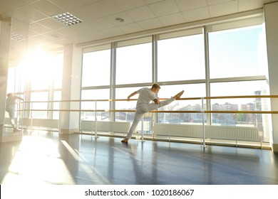 Athlete on first training after getting injured, guy feel pain but continue warm-up. Tattooed male wearing sport clothes standing near ballet barre in hall with big windows and mirrors. Concept of