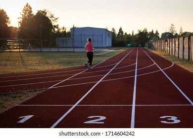 athlete on a running tartan track during summer and sunset
