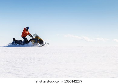 Athlete on a snowmobile moves in the winter in the mountains of the Urals.