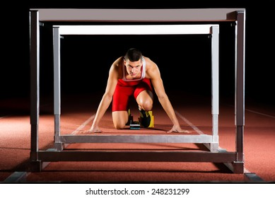 athlete on the starting block in hurdles race