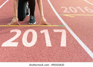 Athlete on starting line waiting for the start in running track with text 2017 year, Start to new year