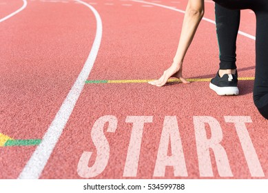 Athlete on starting line waiting for running track with text Start