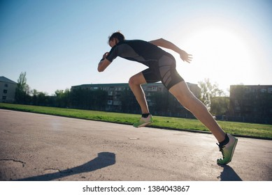 Athlete on the treadmill runs from the start on a sunny day