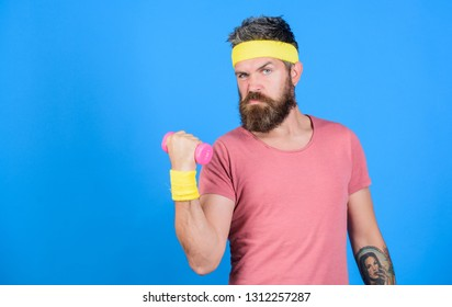 Athlete on way to stronger body. Healthy habits. Sportsman retro outfit training blue background. Athlete training with little dumbbell. Man bearded athlete exercising dumbbell. Motivated athlete guy.