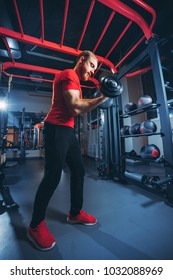the athlete performs exercises with dumbbells in the gym