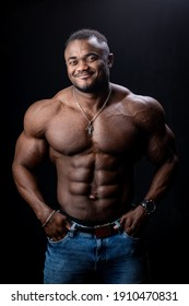 Athlete in phototstudio. Very muscular athlete man shows body to the camera. Perfect muscules. Black background.