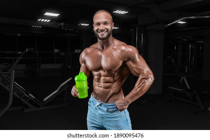 The athlete poses in the gym with a shaker in his hand. Fitness, bodybuilding, powerlifting concept. Mixed media