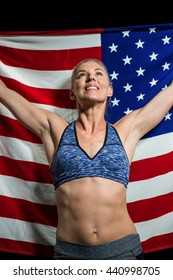 Athlete posing with american flag after victory on black background