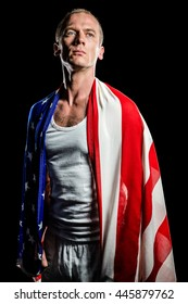 Athlete posing with american flag wrapped around his body on black background