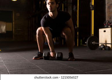 Athlete practicing dumbbell snatches at the gym. Dark photography concept with copy space.