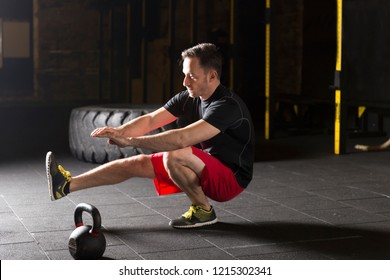 Athlete practicing pistol squats at the gym. Dark photography concept with copy space text area.