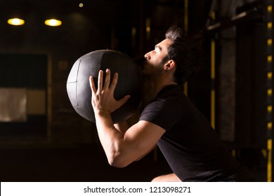 Athlete practicing wall ball shots with a med ball at the gym.