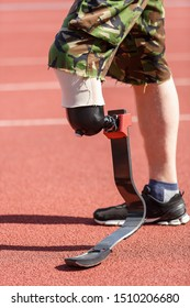 Athlete with prostetic leg exercising on tracks in stadium.Strong man with amputated limb training in gym.Sprinter with prosthesis foot exercises in running marathon