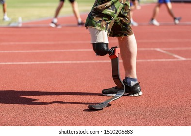 Athlete with prosthetic leg exercising in running on stadium track with other people on background.Strong man with amputated limb training for marathon.Sportsman with prosthesis on foot