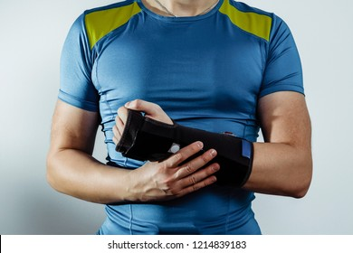 The athlete puts on a protective orthosis. A well-built man covers his hand, joints from damage. Hand stiffening with an orthosis, hand problems, wrist pain. Instead of plaster. Injury at the gym.