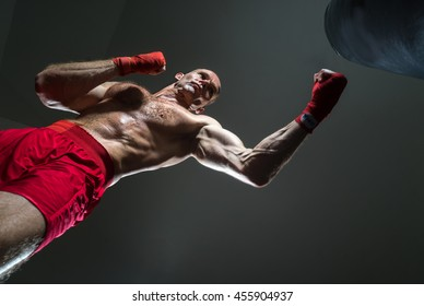 Athlete in red shorts gets in a strike on a large pear