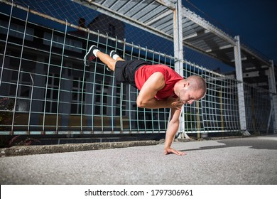 Athlete in a red t-shirt doing one arm handstand push ups at the outdoor gym.