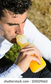 Athlete resting and drinking  to recover sugar , mineral salts and energy with an orange juice. Sportsman with bottle.