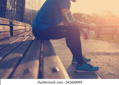 Athlete resting on bench in park at sunset after running with bottle of water (intentional sun glare and vintage color)